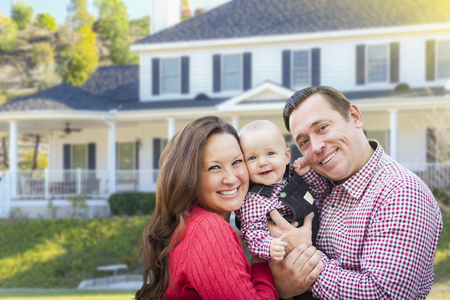 Happy Young Family With Baby Outdoors In Front of Beautiful Custom Home. Stockfoto