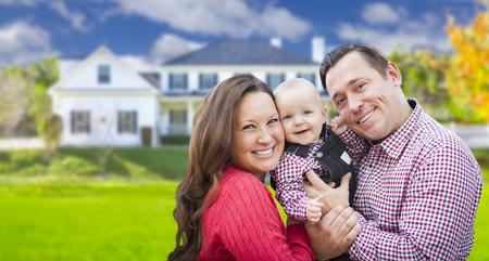 familias felices: Familia joven feliz con el bebé al aire libre delante de bellas vivienda personalizado.