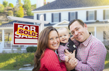 Happy Young Family In Front of For Sale Real Estate Sign and House. Stockfoto