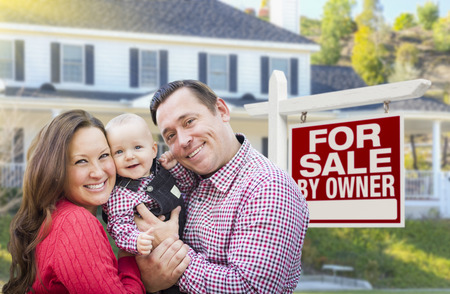 sale sign: Happy Young Family In Front of For Sale By Owner Real Estate Sign and House.
