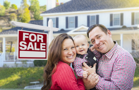 sign in: Happy Young Family In Front of For Sale Real Estate Sign and House. Stock Photo