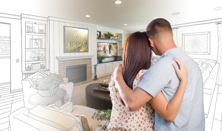 looking over: Curious Young Military Couple Looking Over Custom Living Room Design Drawing Photo Combination. Stock Photo