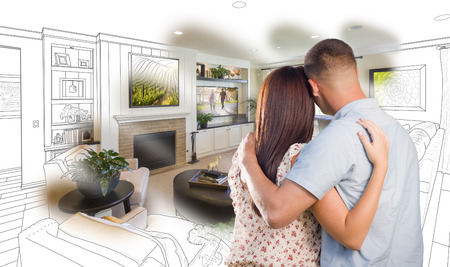 living room design: Curious Young Military Couple Looking Over Custom Living Room Design Drawing Photo Combination. Stock Photo