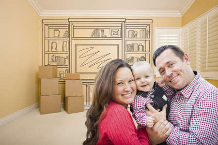 envisioning: Young Family In Room With Moving Boxes and Drawing of Entertainment Unit On Wall. Stock Photo