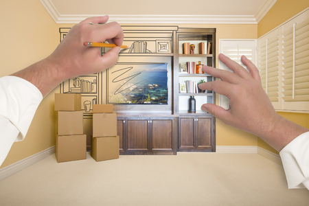 drawing room: Hands Drawing Beautiful Entertainment Unit In Room With Moving Boxes.