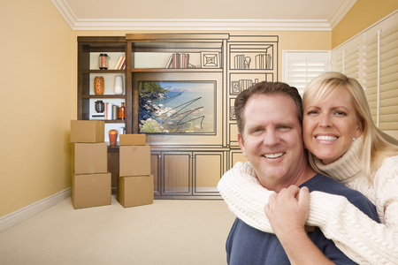 envisioning: Young Couple In Room With Moving Boxes and Drawing of Entertainment Unit On Wall.