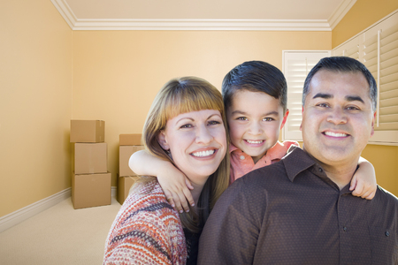 family  room: Happy Young Mixed Race Family In Room With Moving Boxes.