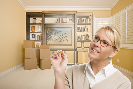 envisioning: Female Holding Pencil In Room With Moving Boxes and Drawing of Entertainment Unit On Wall. Stock Photo