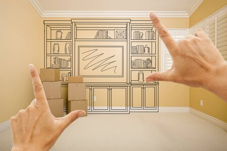 drawing room: Hands Framing Drawing of Entertainment Unit In Empty Room With Moving Boxes.