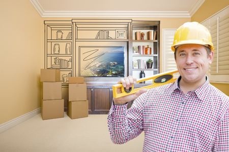 envisioning: Male Construction Worker Wearing Hard Hat In Room With Drawing of Entertainment Unit On Wall.