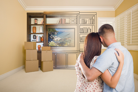 envisioning: Young Military Couple Looking At Drawing of Entertainment Unit In Room With Moving Boxes.