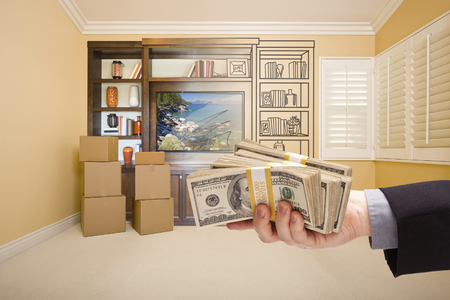 envisioning: Hand Holding Out Cash Over Drawing of Entertainment Unit In Room With Moving Boxes.