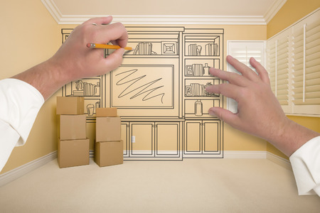 construction draftsman: Hands Drawing Beautiful Entertainment Unit In Room With Moving Boxes.