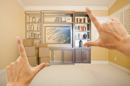 drawing room: Hands Framing Drawing of Entertainment Unit Gradating Into Photograph In Room With Moving Boxes.