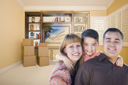 envisioning: Happy Young Mixed Race Family In Room With Moving Boxes and Drawing of Entertainment Unit on Wall.
