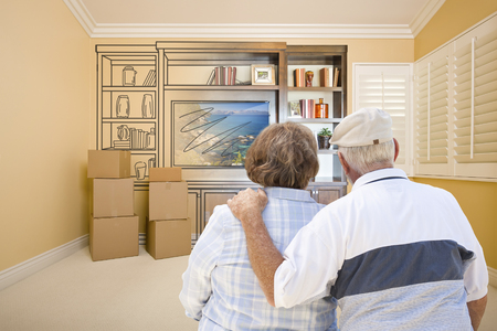 senior home: Senior Couple In Room With Moving Boxes Looking At Drawing of Entertainment Unit.