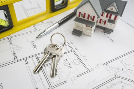 model home: Model Home, Construction Level, Engineer Pencil and Keys Resting on Custom House Plans.