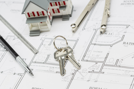 do it yourself: Model Home, Pencil, Ruler, Compass and Key Resting on Custom House Plans.