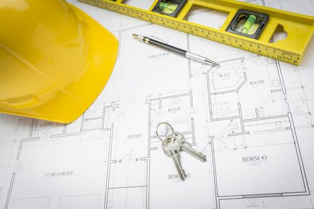 residential homes: Construction Hard Hat, Pencil, Level and Keys Resting on Custom House Plans.