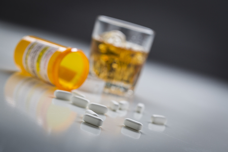 Several Prescription Drugs Spilled From Fallen Bottle Near Glass of Alcohol. Banque d'images