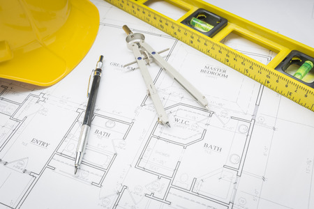 Construction Hard Hat, Pencil, Level and Compass Resting on Custom House Plans.