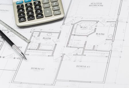 cost: Pencil, Ruler and Calculator Resting on Custom House Plans.