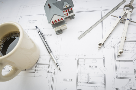 model home: Model Home, Cup of Coffee, Pencil, Ruler and Compass Resting on Custom House Plans. Stock Photo