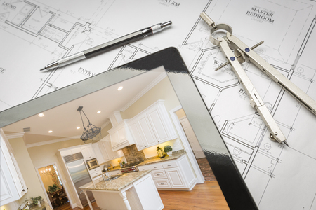 finished: Computer Tablet Showing Finished Kitchen Sitting On House Plans With Pencil and Compass.