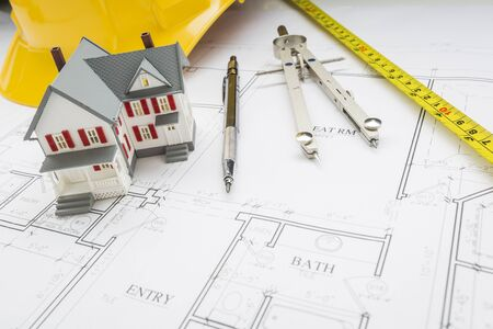 model home: Model Home, Measuring Tape, Hard Hat, Pencil and Compass Resting on Custom House Plans. Stock Photo