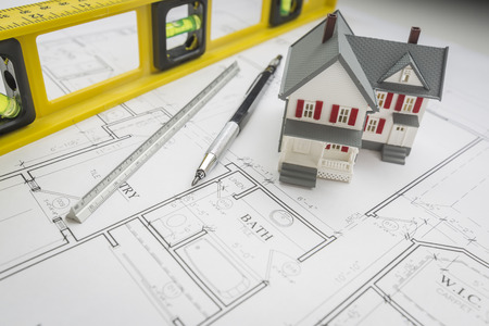 model home: Model Home, Construction Level, Engineer Pencil and Ruler Resting on Custom House Plans.