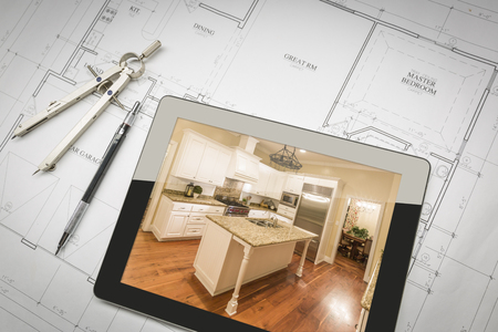 renovations: Computer Tablet Showing Finished Kitchen Sitting On House Plans With Pencil and Compass.