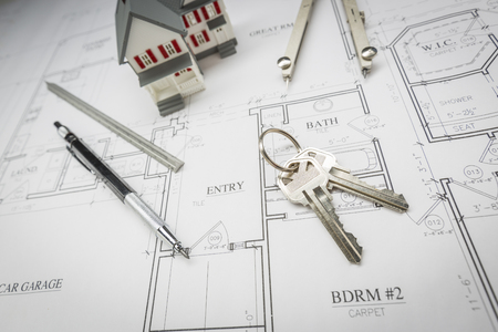 Model Home, Pencil, Compass, Ruler and Keys Resting On Custom House Plans.