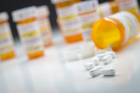 drug: Variety of Medicine Bottles Behind Pills Spilling From Fallen Bottle. Stock Photo