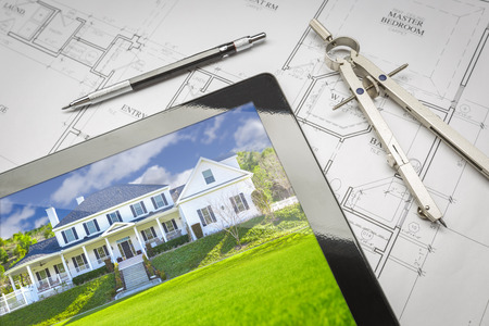Computer Tablet Showing Finished House Sitting On House Plans With Pencil and Compass.