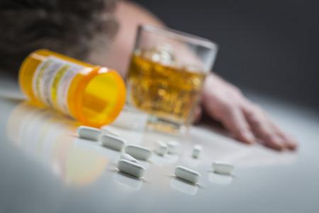drogadiccion: El hombre inconsciente boca abajo detrás de los medicamentos con receta y dispersas vaso de alcohol. Foto de archivo