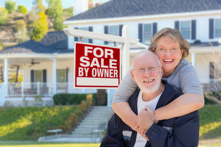 home for sale: Senior Adult Couple in Front of Home For Sale Real Estate Sign and Beautiful House.