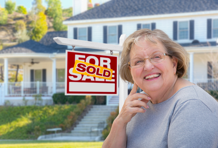 real estate sold: Senior Adult Woman in Front of Sold Home For Sale Real Estate Sign and Beautiful House. Stock Photo
