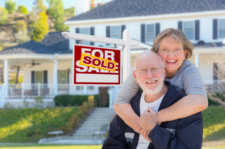 home for sale: Senior Adult Couple in Front of Sold Home For Sale Real Estate Sign and Beautiful House.