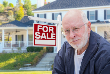 home for sale: Senior Adult Man in Front of Home For Sale Real Estate Sign and Beautiful House. Stock Photo