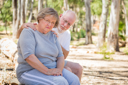 squabble: Very Upset Senior Woman Sits With Concerned Husband Outdoors. Stock Photo