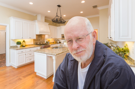 80s adult: Happy Senior Man Sitting In Custom Kitchen Interior.