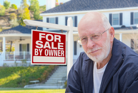 home sale: Senior Adult Man in Front of Home For Sale By Owner Real Estate Sign and Beautiful House.