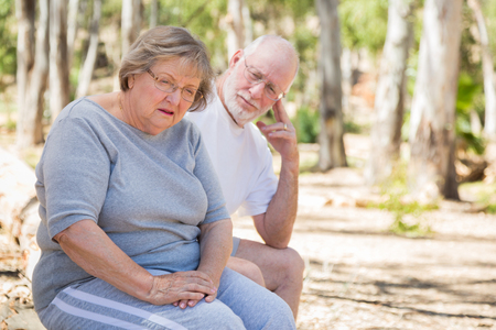 Very Upset Senior Woman Sits With Concerned Husband Outdoors. Stock Photo
