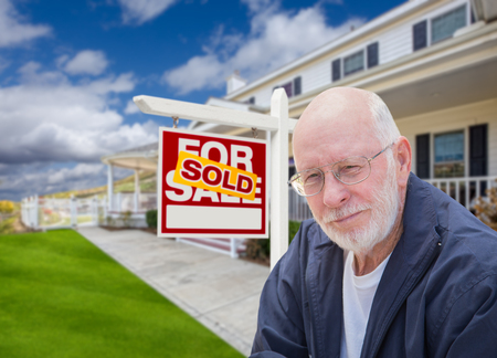real estate sold: Senior Adult Man in Front of Sold Home For Sale Real Estate Sign and Beautiful House.