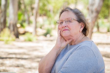 soledad: Upset Senior Woman Sitting Alone Outside.
