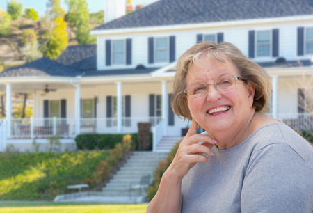 senior adult woman: Senior Adult Woman in Front of Beautiful House. Stock Photo
