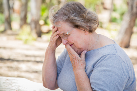 sadness: Upset Senior Woman Sitting Alone Outside.
