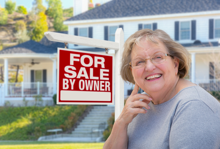new ages: Senior Adult Woman in Front of Home For Sale By Owner Real Estate Sign and Beautiful House.