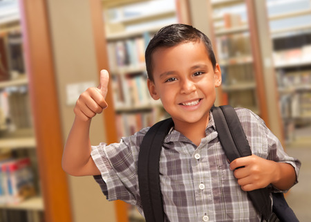 back pack: Handsome Hispanic Student Boy with Back Pack and Thumbs Up in the Library. Stock Photo