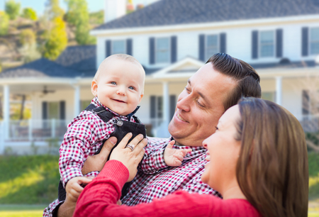 house family: Adorable Little Baby Boy Having Fun With Mother and Father In Front Yard Of House.